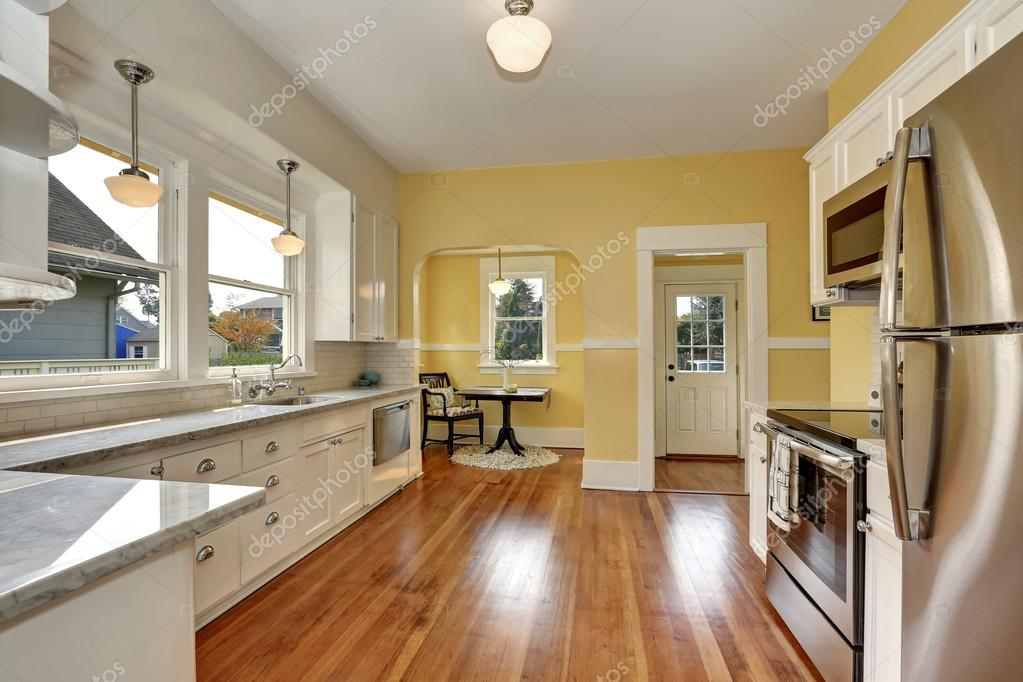 Kitchen interior with white cabinets, yellow walls and ...