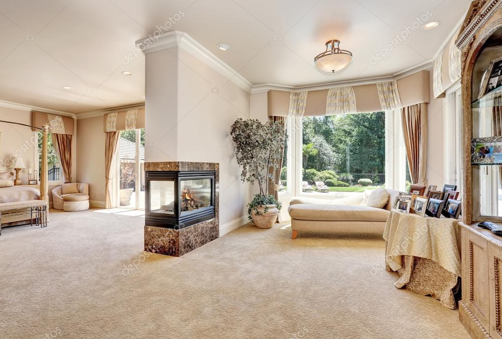 Large Master Bedroom In Luxury Home With Doors To Balcony. Glass Fireplace  With Burning Fire. Comfortable Sitting Area With Cream Chaise Lounge.