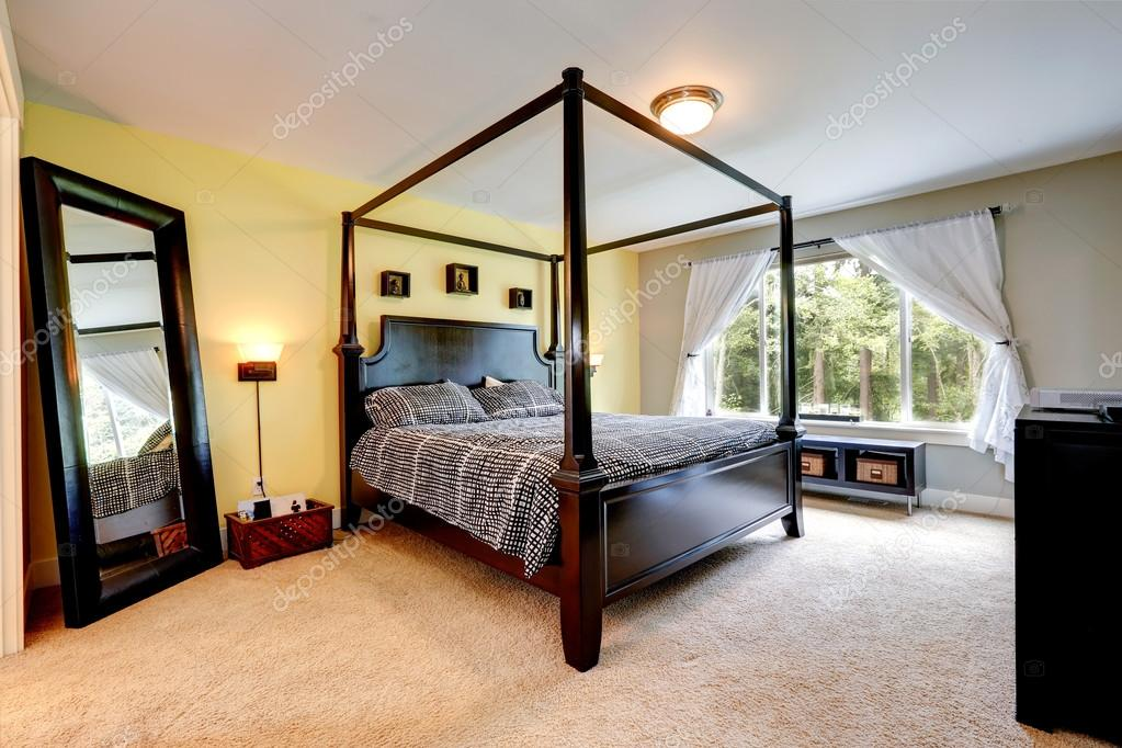 cama de madera tallada con postes de altas. interior de dormitorio ...
