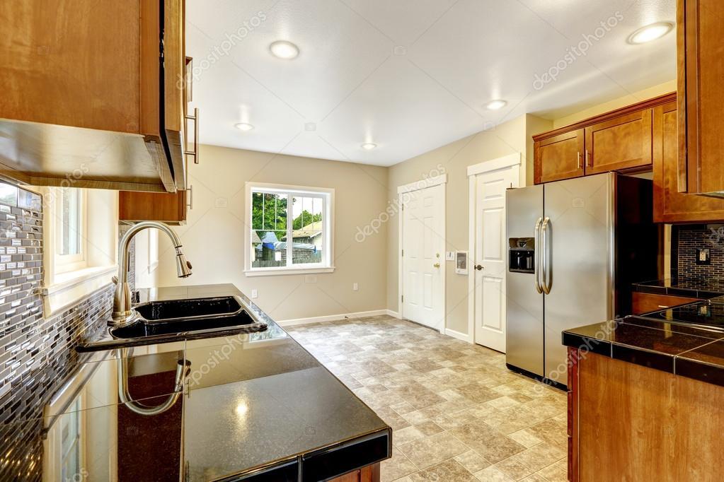 cocina con encimeras de granito negro y gabinetes de madera u foto de stock