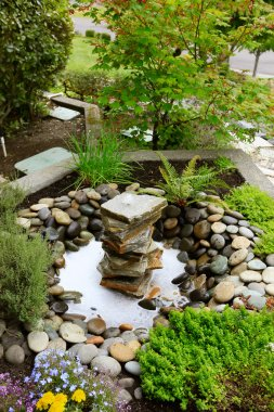 Ideas for landscaping home garden. Fountain with rocks