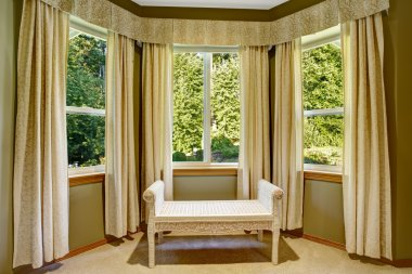 Round corner with windows and wicker ottoman