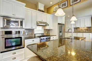 Kitchen room with granite tops and  white storage combination