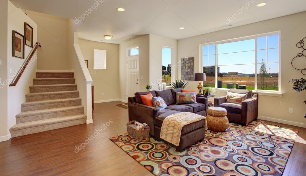 Soggiorno con divano marrone e tappeto allegro u foto stock
