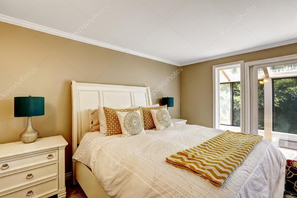 beau lit blanc avec literie de tons clairs et les détails orange ...