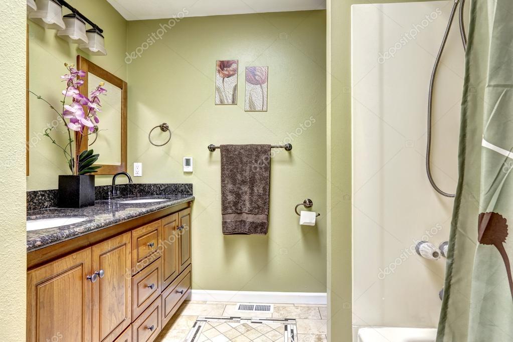 Heldere badkamer licht groene toon houten kast met graniet