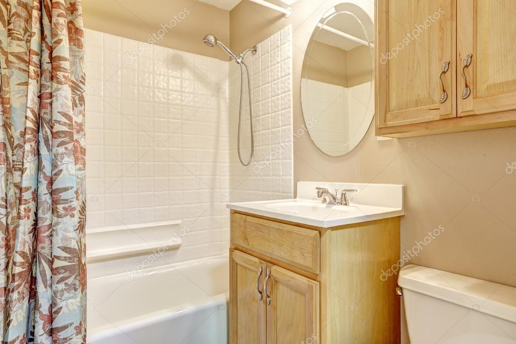 licht beige badkamer met houten kasten en floral gordijn — Stockfoto ...