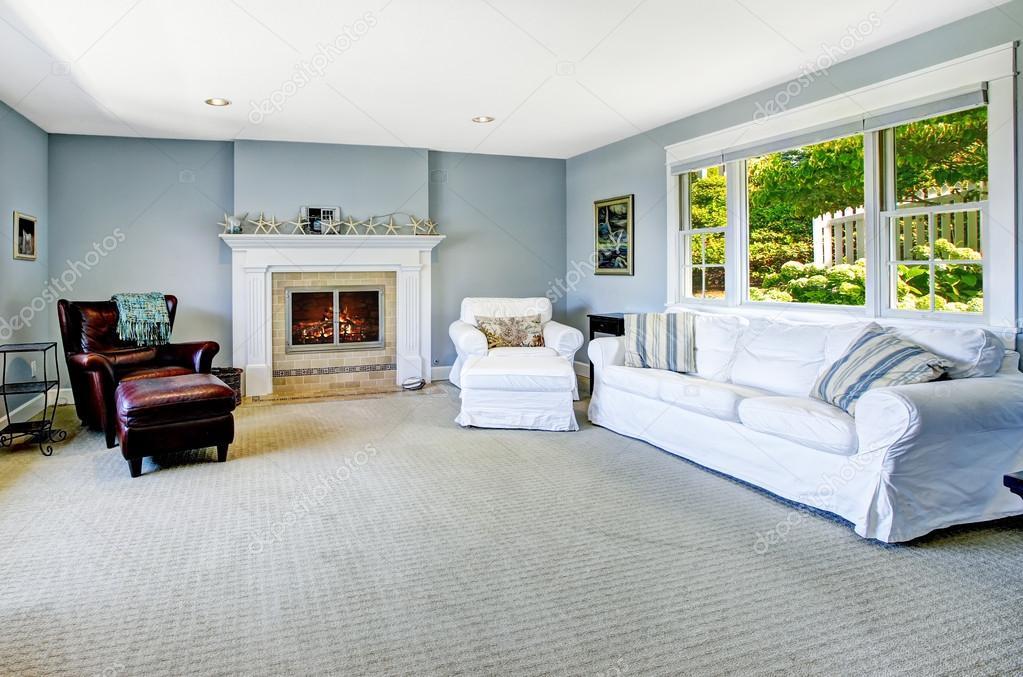Licht blauw woonkamer met witte slaapbank en open haard ...
