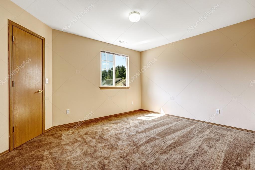 Ivoire chambre vide avec une moquette marron et porte en bois ...