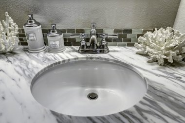 Bathroom vanity cabinet with white granite top. Sink and decorat