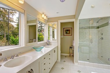 Spacious bright bathroom with glass door shower