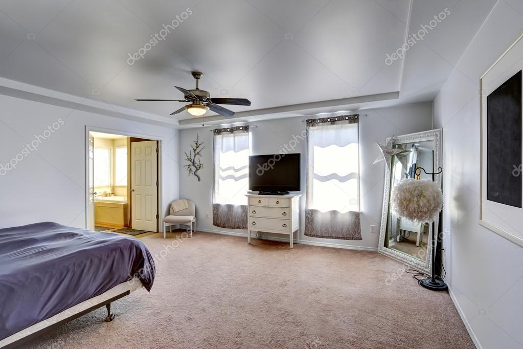 Master slaapkamer met tv en grote spiegel in de hoek