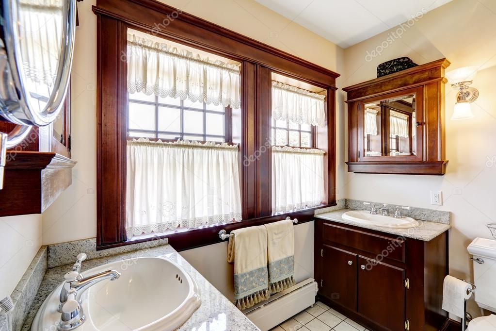 salle de bain avec armoires bruns foncés et grande fenêtre ...