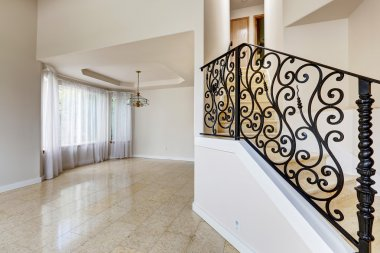 Emtpy house interior. Marble staircase with black wrought iron r