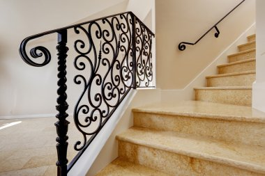 Marble staircase with black wrought iron railing