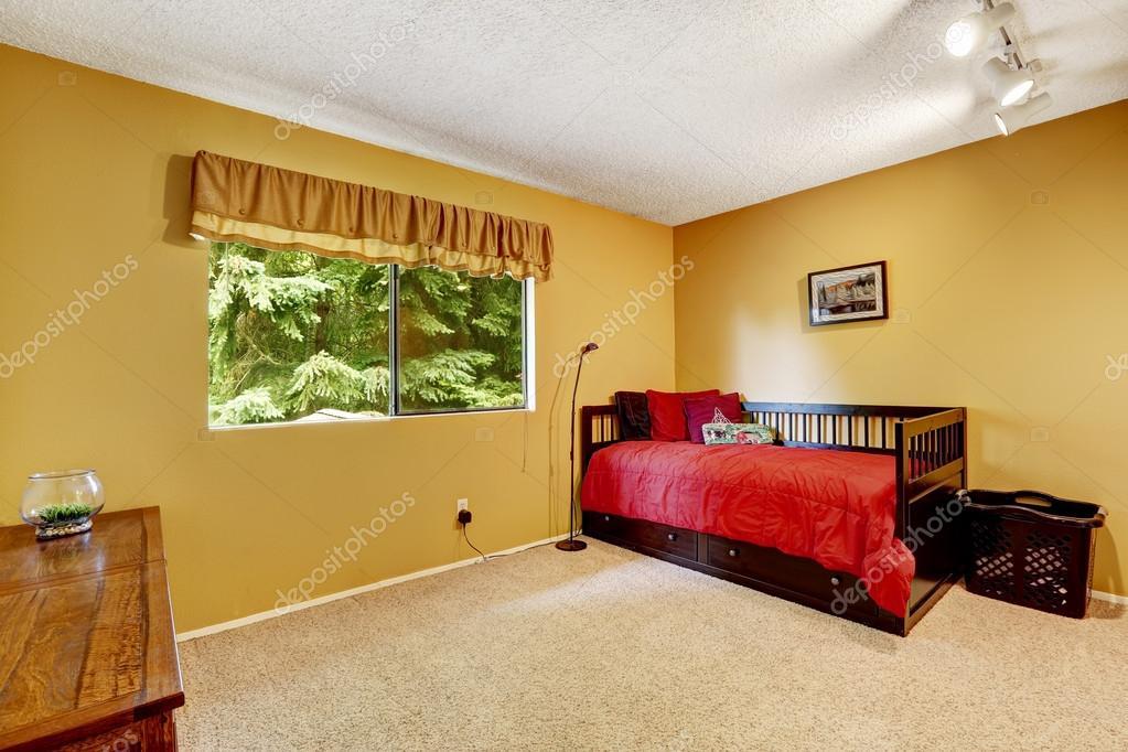 Lumineux chambre jaune avec lit en bois noir — Photographie ...