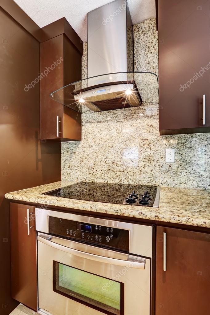 aparato de cocina moderna campana de acero con cristal y luces en mezcla con estufa de acero con la superficie brillante negra plano u foto