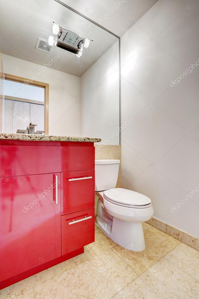 Bright bathroom interior with marble tile floor and red bathroom vanity cabinet with granite top and large mirror — Photo by iriana88w