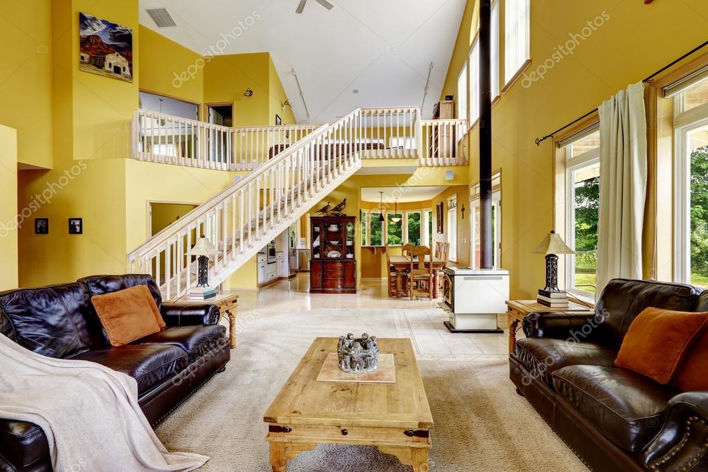 casa de lujo con alto techo abovedado y altillo con escalera de madera espaciosa sala familiar con sofs de cuero y estufa antigua u foto de irianaw