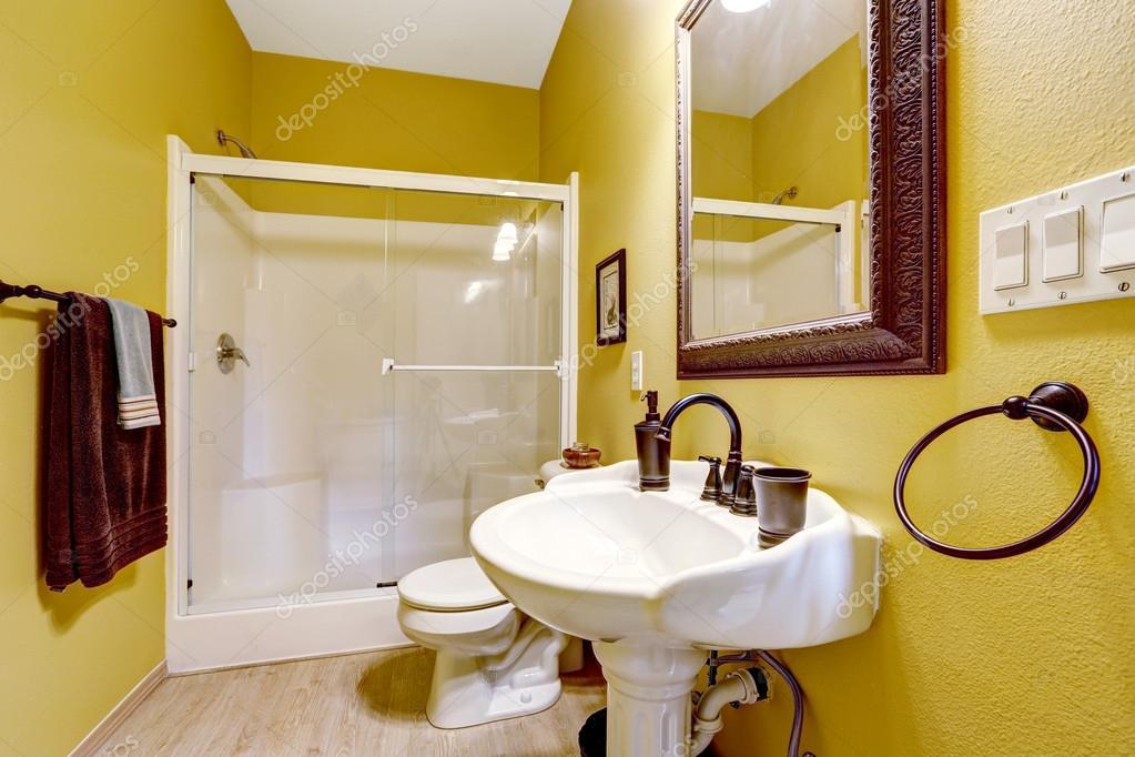 Salle de bains jaune lumineuse avec douche porte vitrée ...