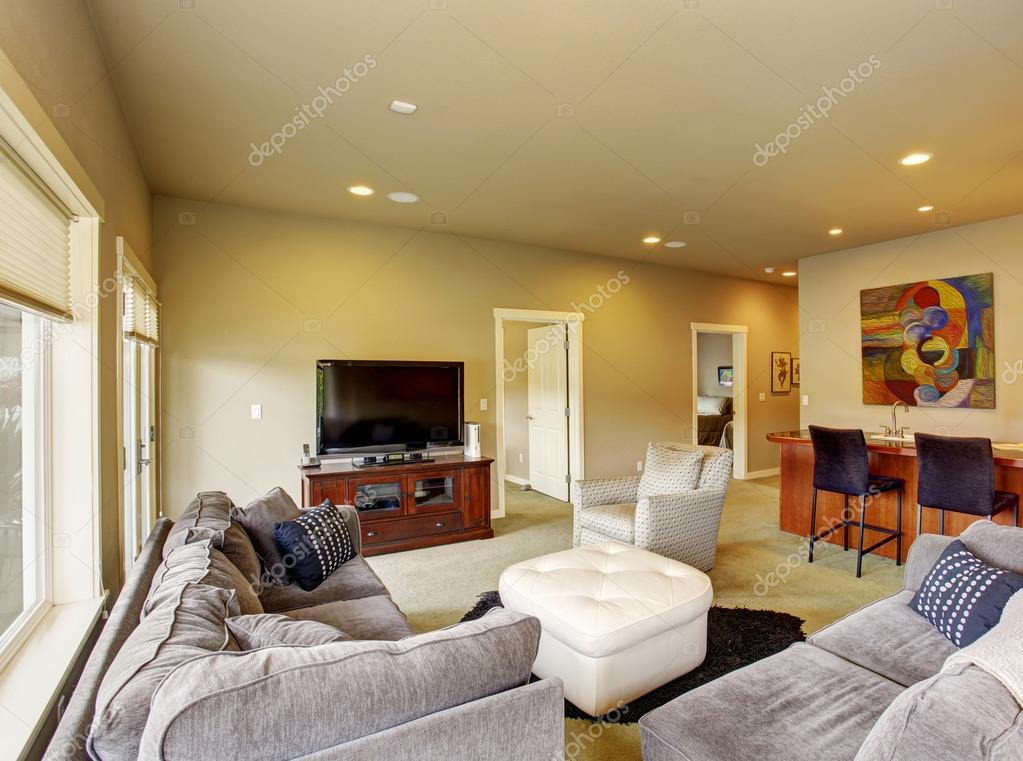 Secundaire woonkamer met tapijt en zwarte bar met krukken ...