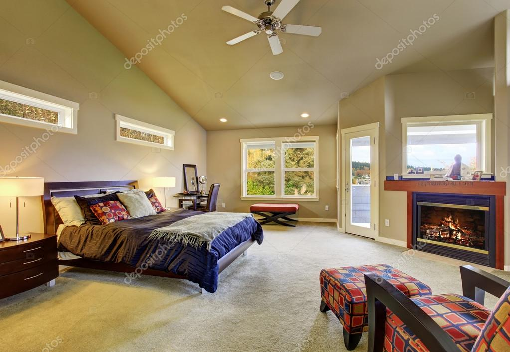Master bedroom with windows and fireplace.