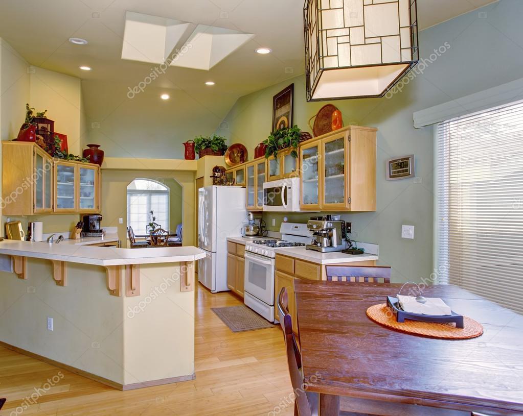 Cocina modernizada con luz verde las paredes y piso de madera ...
