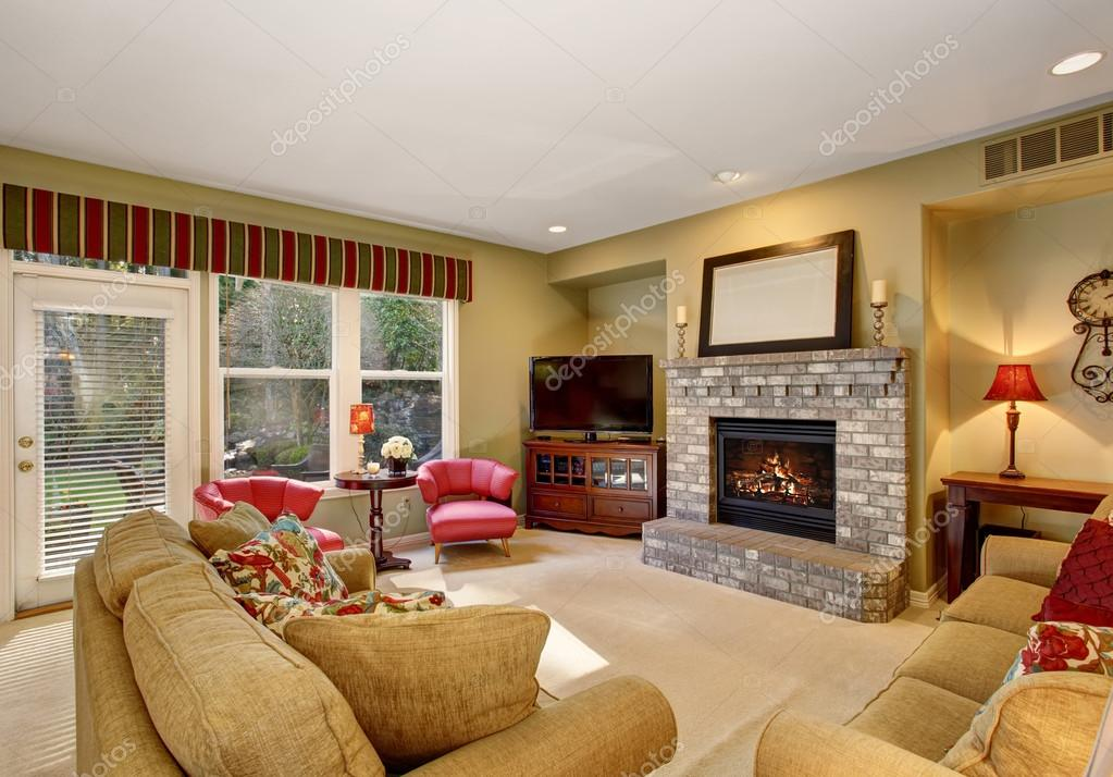 Cozy family living room with red chairs and fireplace for Beautiful chairs for living room