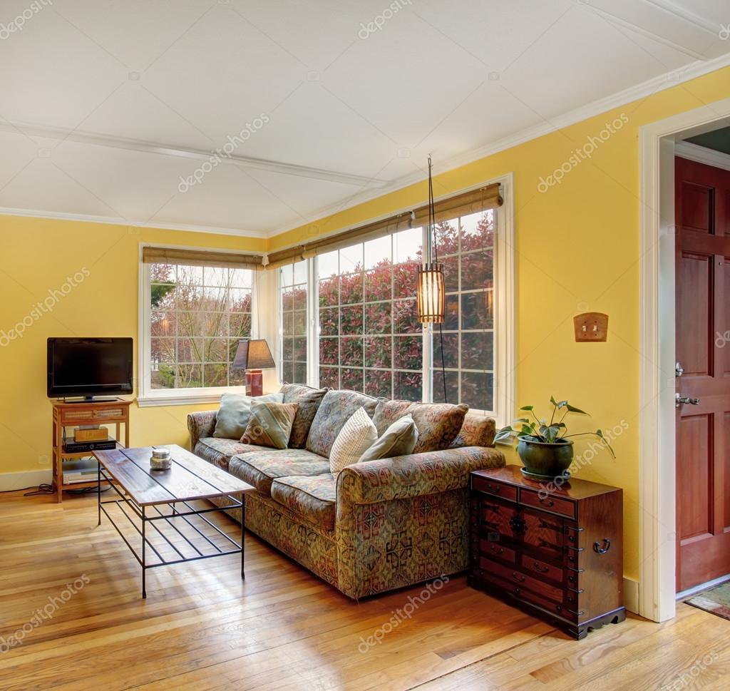 Soggiorno in parquet con divano colorato e le pareti gialle — Foto ...