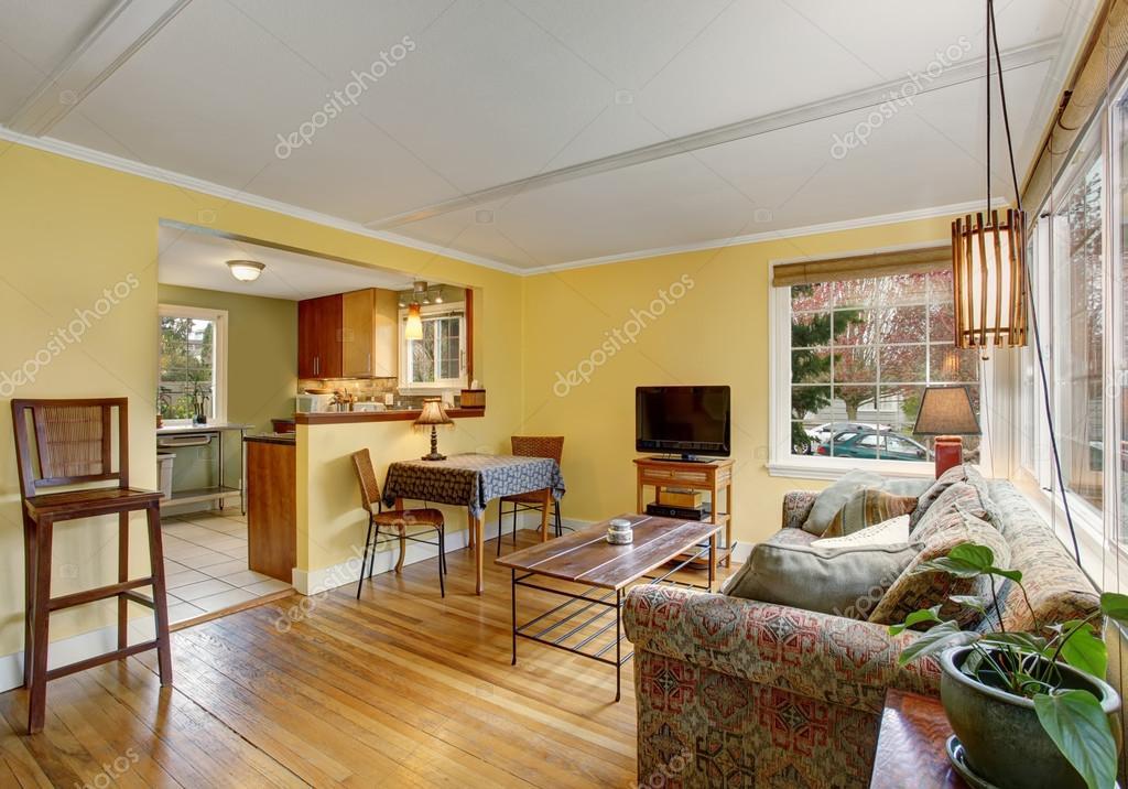 Mooie hardhouten woonkamer met kleurrijke sofa, en gele muren ...