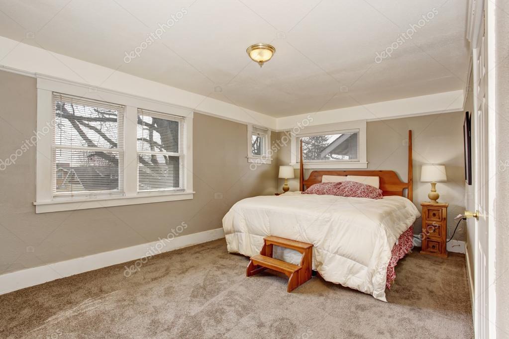 Zeer eenvoudige kamer met grijs bruin muren, en witte beddengoed ...