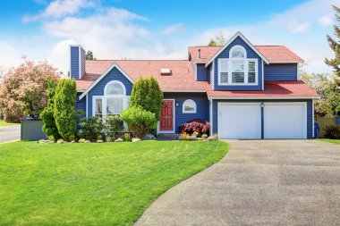 Large blue house with white trim and a nice lawn.