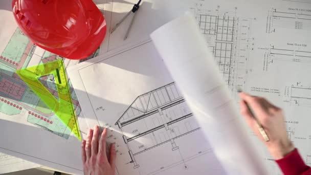Architekt faltet Bauplan auf und markiert ihn mit Bleistift. Ansicht von oben