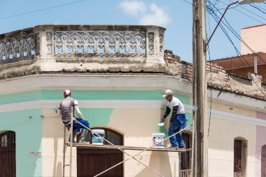 Men painting a facade of a colonial house.
