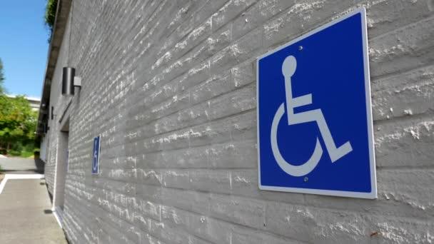 Mozgó mozgássérült parkoló tábla a falon
