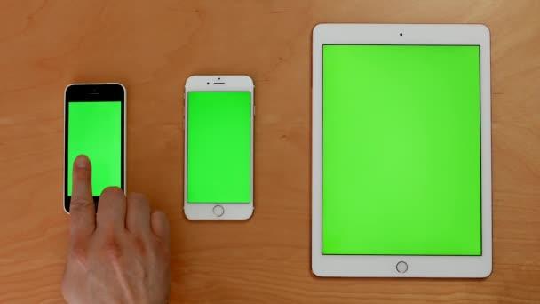Nahoru shot ruka dotykové telefony a ipad na zelené obrazovce