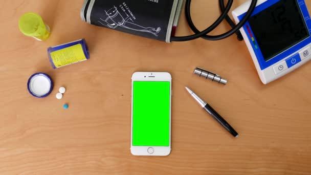 Nahoru shot člověka pomocí iphone s různými gesty rukou na zelené obrazovce s krevní tlak a léky na stole