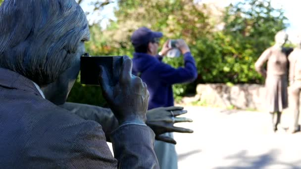 People sightseeing and taking picture with statue at Queen Elizabeth Park