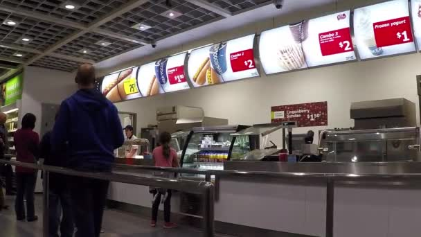 People line up for ordering meal at food court cafeteria.
