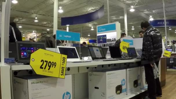 People trying apple computer inside Best buy store with wide angle camera shot