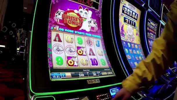 Zavřít lidi hrát automat a lisování hotovost tlačítko uvnitř Hard Rock Casino v Coquitlam Bc Kanada s širokým úhlem záběru