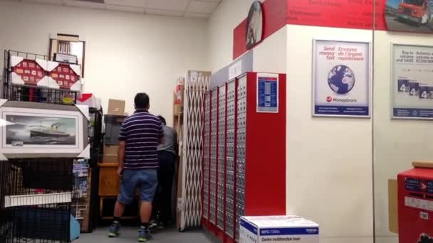 Lidé vyhnou prázdné pole pro poštu uvnitř poštovního úřadu