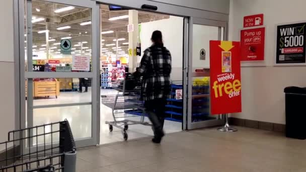 People with Shopping Cart Walking Through the Doors at superstore in Coquitlam BC Canada.