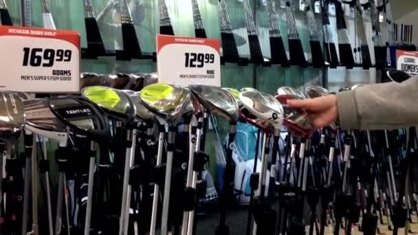 Frau wählt Golfschläger in Golfabteilung