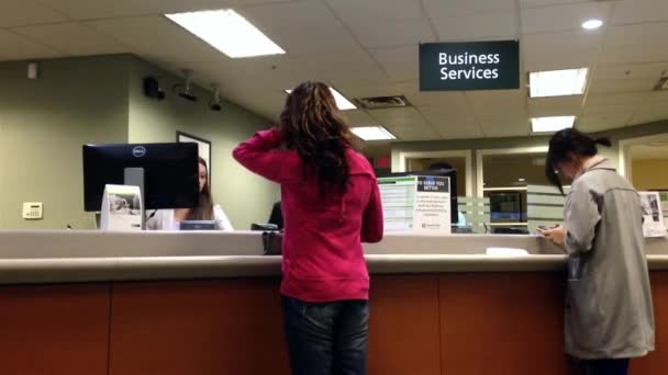 People at business service counter talking to the teller inside TD Bank