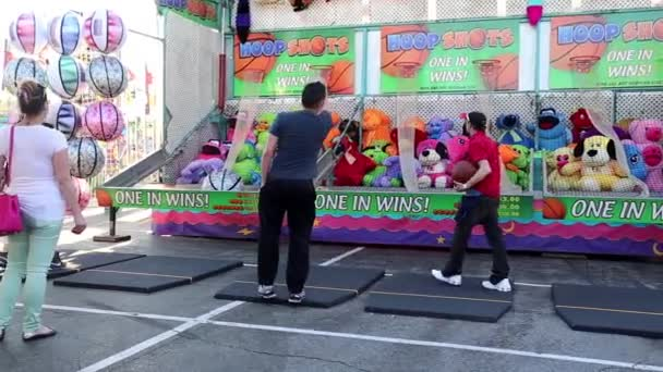 People playing basketball shooting game for winning animal doll at the West Coast Amusements Carnival