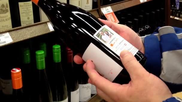 Ruka má lahví vína Chile z poličky