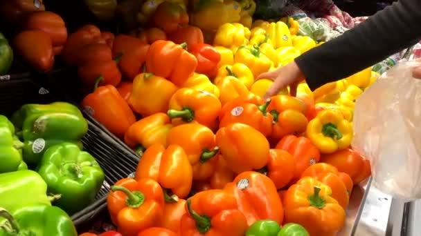 Žena v obchodě vyberete žlutá paprika vyrábět oddělení