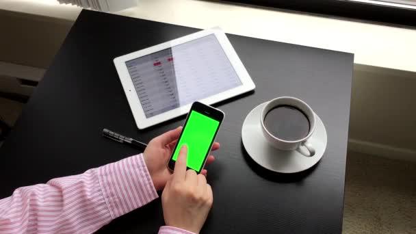 Žena držící zelené obrazovky iphone s globální směnný kurz aplikace na ipad s rozlišením 4 k