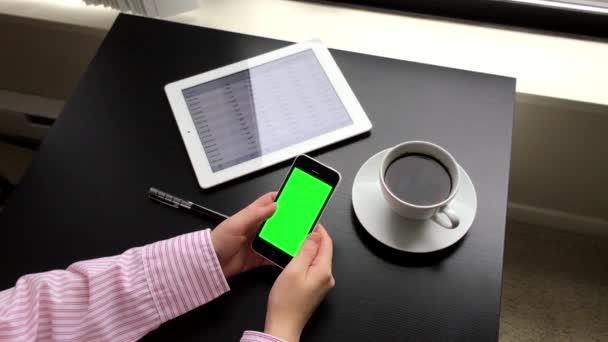 Žena držící zelené obrazovky iphone s globální směnný kurz aplikace na ipad